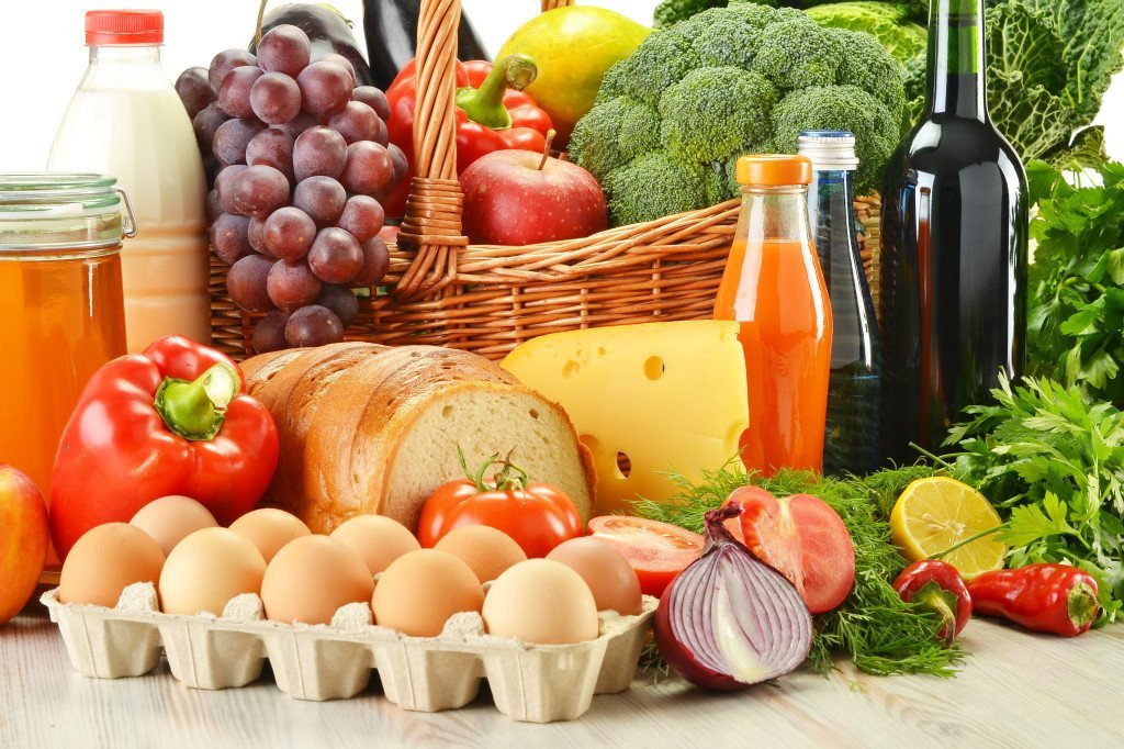 Groceries in wicker basket including vegetables and fruits