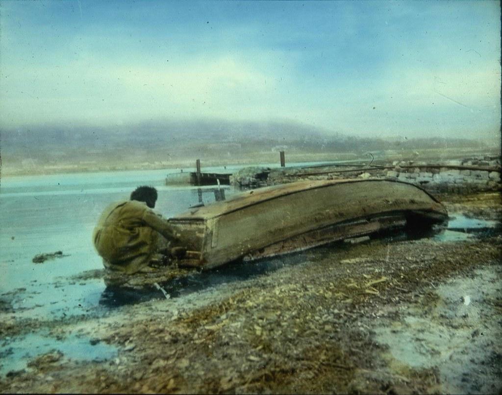 Мужчина чинит лодку во Владивостоке