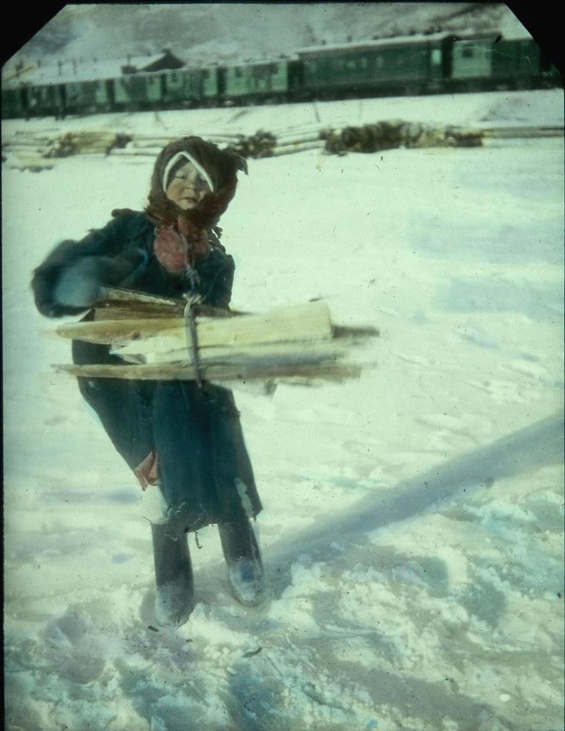 Ребенок несет дрова где-то в Сибири